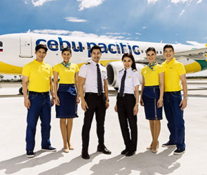 Cebu Pacific cabin crew pose in their new uniforms, in front of a Cebu Pacific plane